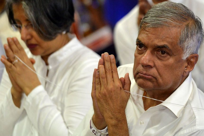 Wickremesinghe and his wife Maitree offer prayers at a temple in Colombo on April 4, 2018.