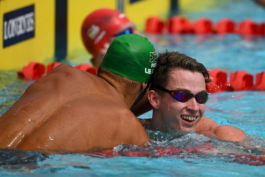 South Africa's Chad Le Clos and England 's Benjamin Proud (right) congratulate each other after the swimming men's 50m butterfly qualifications during the 2018 Gold Coast Commonwealth Games at the Optus Aquatic Centre on April 5, 2018.