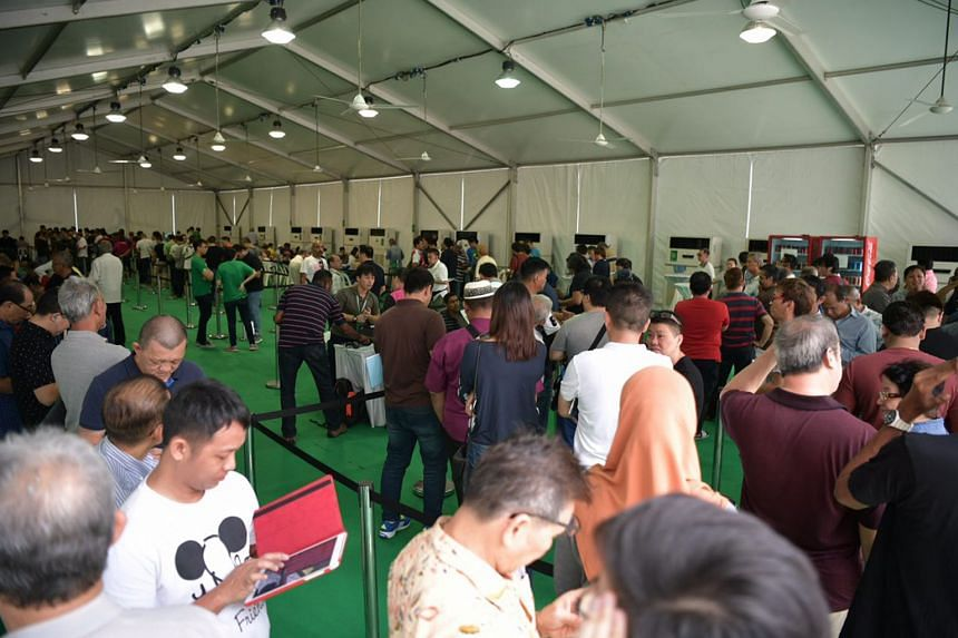 People queue up to register themselves as Grab drivers at the open-air carpark of Midview City, where Grab's driver centre is located.