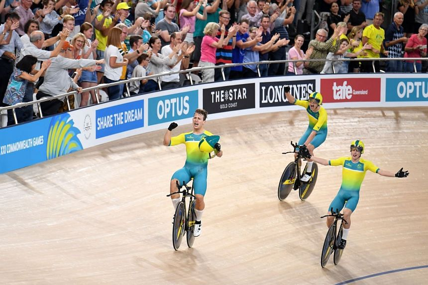 Australian cyclists Sam Welford, Kelland O'Brien and Alex Porter celebrate winning gold and breaking the world record in the men's team pursuit final event on day one of the Commonwealth Games on April 5, 2018.
