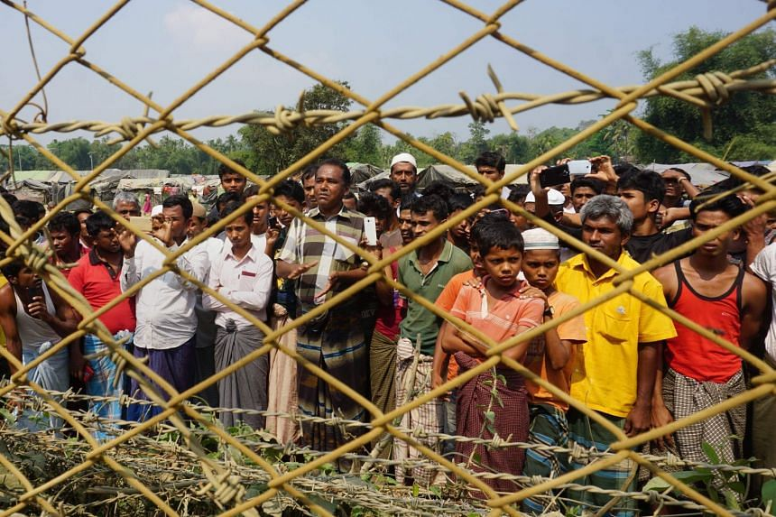 Rohingya Muslims gather behind Myanmar's border lined with barbed wire fences in Maungdaw district in Rakhine state on March 18, 2018.