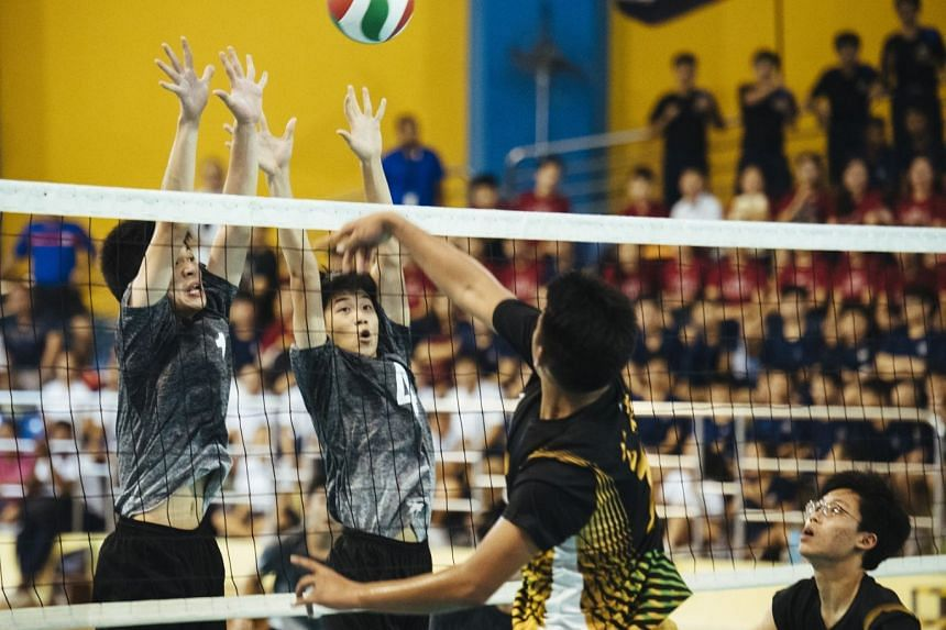 (From left) Avan Cheah and Jaron Lee of St. Hilda's Secondary School block a spike from Catholic High School's Alastair Chan during the B Division national volleyball finals at Woodlands Sports Hall on April 5, 2018.