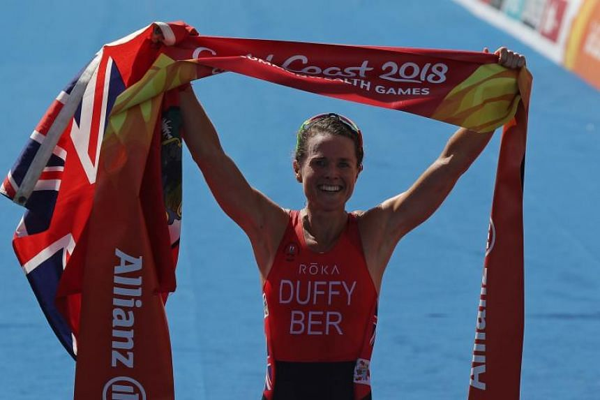 Flora Duffy of Bermuda celebrates after crossing the finish line in first place.