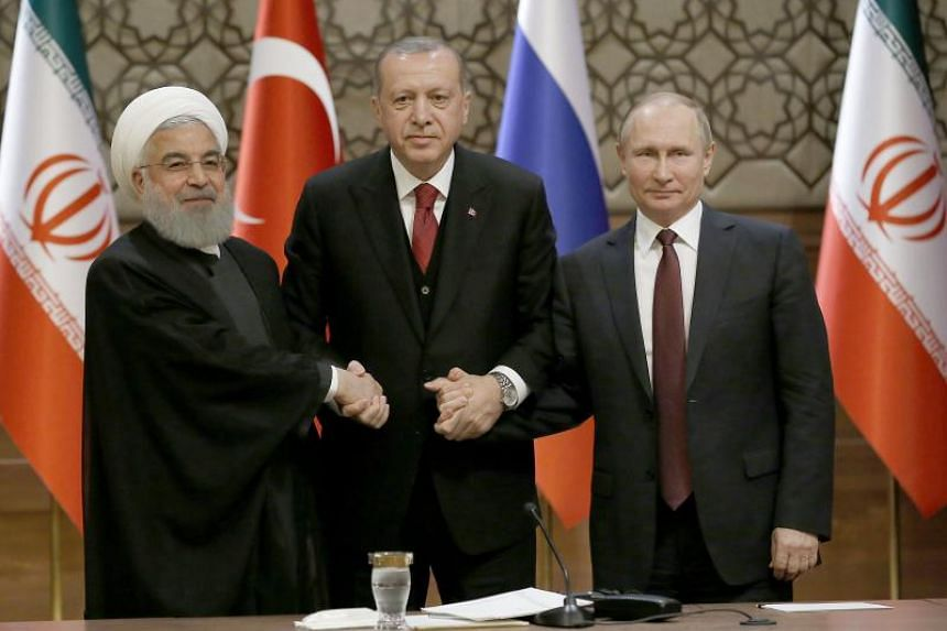 From left to right: Iranian President Hassan Rouhani, Turkish President Recep Tayyip Erdogan and Russian President Vladimir Putin shake hands during a press conference after their meeting at the Presidential Palace in Ankara, Turkey, on April 4, 2018