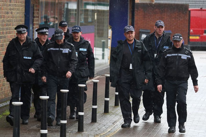 Police officers walk through Salisbury in Britain, close to where Skripal and her father were found poisoned.