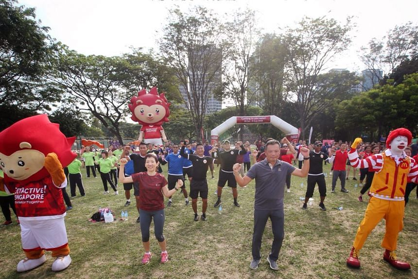 Minister for Culture, Community and Youth Grace Fu (centre) take part in exercises during the sporting day-out for more than 100 McDonald's employees at West Coast Park on April 6, 2018.