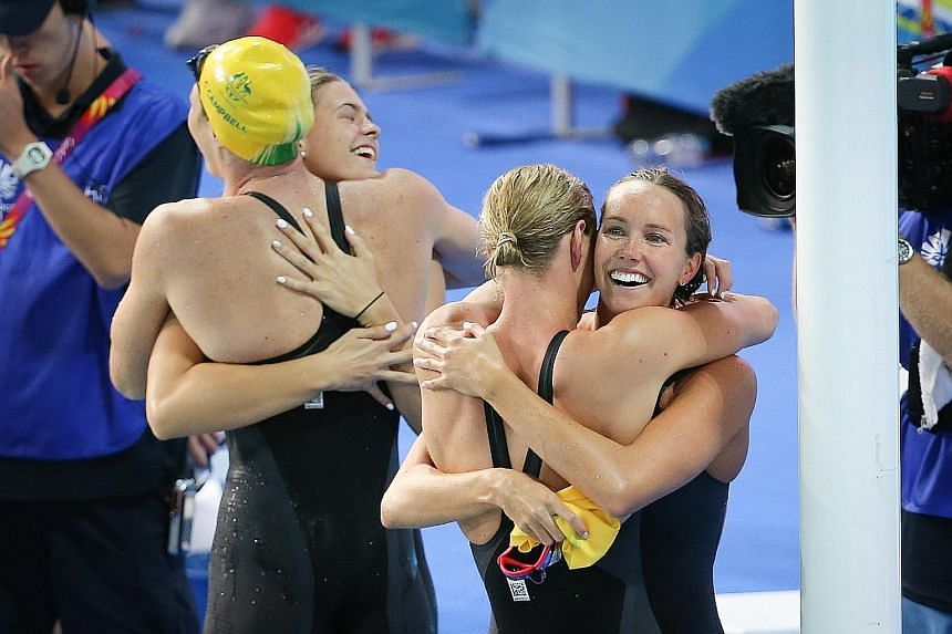 Emma McKeon (right) embracing Bronte Campbell as Shayna Jack does the same with Cate Campbell after the Australian quartet ended the day at the Optus Aquatic Centre by winning the 4x100m freestyle relay in 3min 30.05sec, a world record. It was the ho