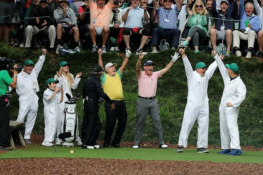 Jack Nicklaus (in yellow) celebrating after his grandson Gary made a hole-in-one on the ninth and final hole during the Masters Par-3 contest at Augusta National, as Gary Player (in black) and eventual winner Tom Watson join in the celebrations.