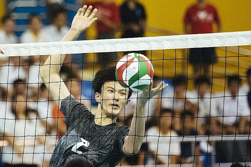 Avan Cheah (left) and Jaron Lee of St Hilda's Secondary blocking a spike from Catholic High's Alastair Chan in the B Division volleyball final at Woodlands Sports Hall yesterday.