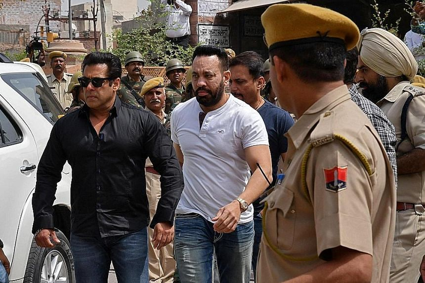Bollywood actor Salman Khan (far left) arriving at a court in Jodhpur in the western Indian state of Rajasthan yesterday. Khan, best known for his macho roles, spent a week in prison in 1998 when first accused of using unlicensed arms to shoot the bl