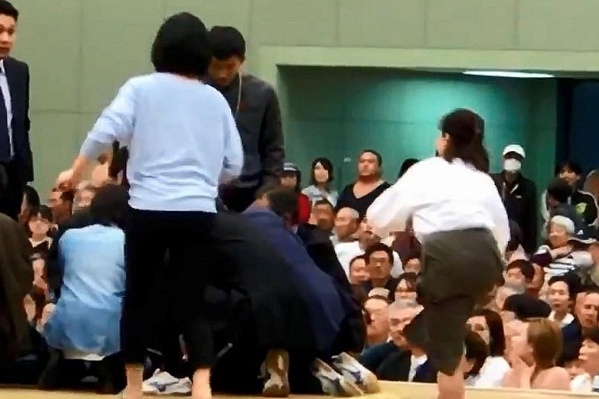 A photo grab from a Youtube video showing women in a sumo ring helping Maizuru mayor Ryozo Tatami, who collapsed while making a speech. Women are forbidden from entering the ring, which is regarded as sacred.