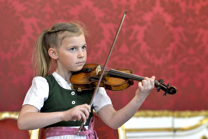 Anna Cacilia Pfoess plays a violin used by Mozart in front of Austrian President Alexander Van der Bellen.
