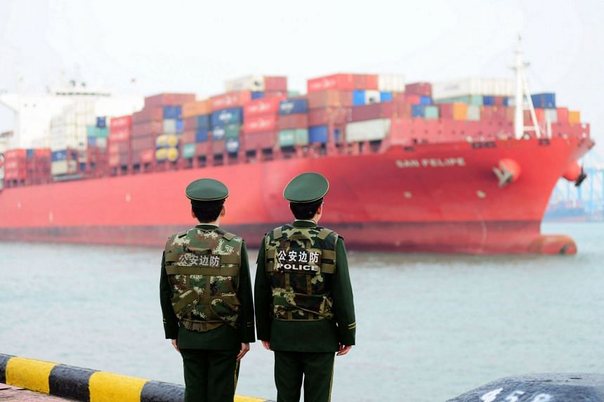 Border guards work at a container port in Qingdao, China on March 8, 2018.