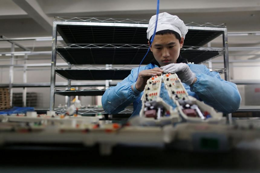 A labourer works inside an electronicsfactory in Qingdao, Shandong province, China.