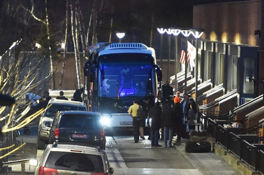 US diplomats and their families prepare to board a bus to leave the US Embassy compound in Moscow.