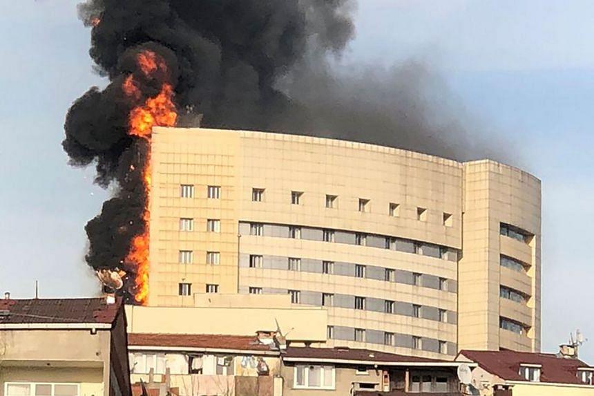 Flames and black smoke engulf the multi-storey hospital.