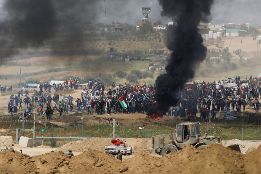 Black smoke rises while Palestinians protest on the Gaza side of the border on April 6, 2018.