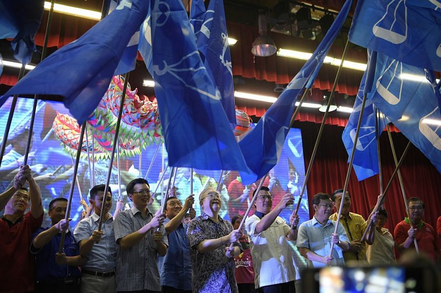 Malaysian Chinese Association (MCA) president Liow Tiong Lai (centre right) and Ayer Hitam (Johor) MP Wee Ka Siong (centre left) wave MCA flags with other party members after a rally in Johor Jaya on March 18, 2018.