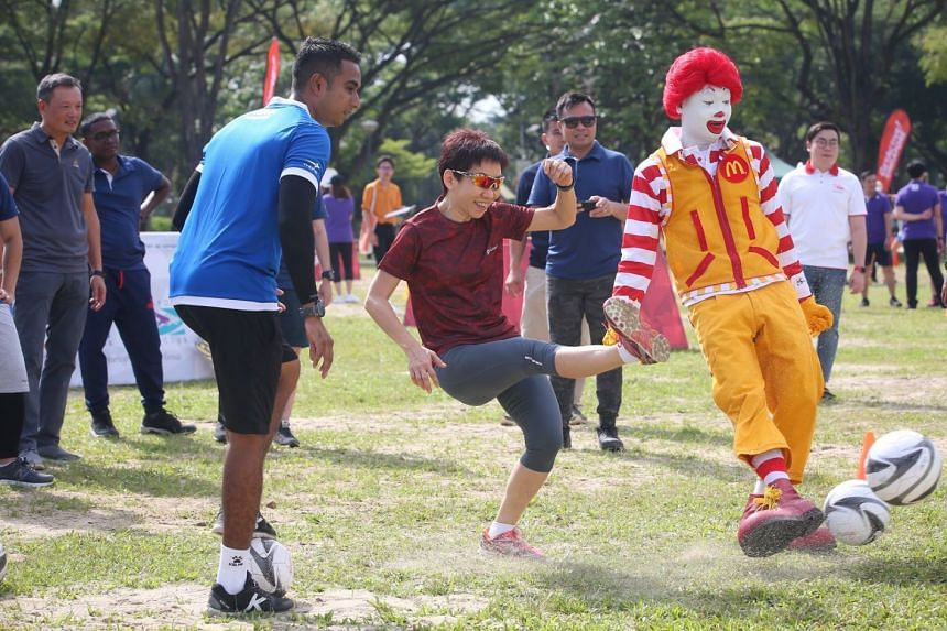 Minister for Culture, Community and Youth Grace Fu (centre) tries to kick a ball into a net at the sporting day-out for more than 100 McDonald's employees at West Coast Park on April 6, 2018.