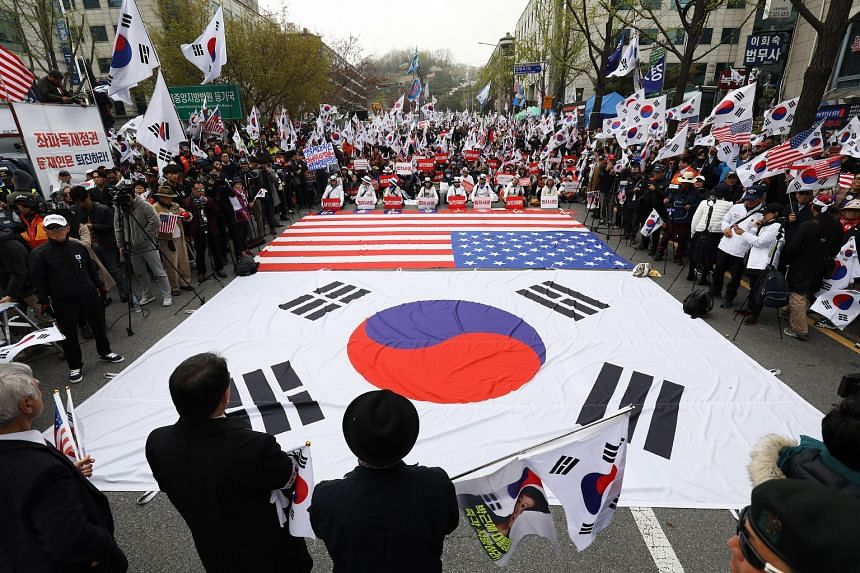 Supporters of former South Korean President Park Geun Hye gather around the South Korean and American flags as they protest outside the Seoul Central District Court in Seoul, on April 6, 2018.