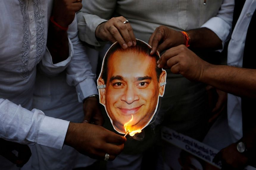 Activists of the youth wing of India's main opposition Congress party burn a cut-out with an image of billionaire jeweller Nirav Modi during a protest in Mumbai, India, on Feb 23, 2018.