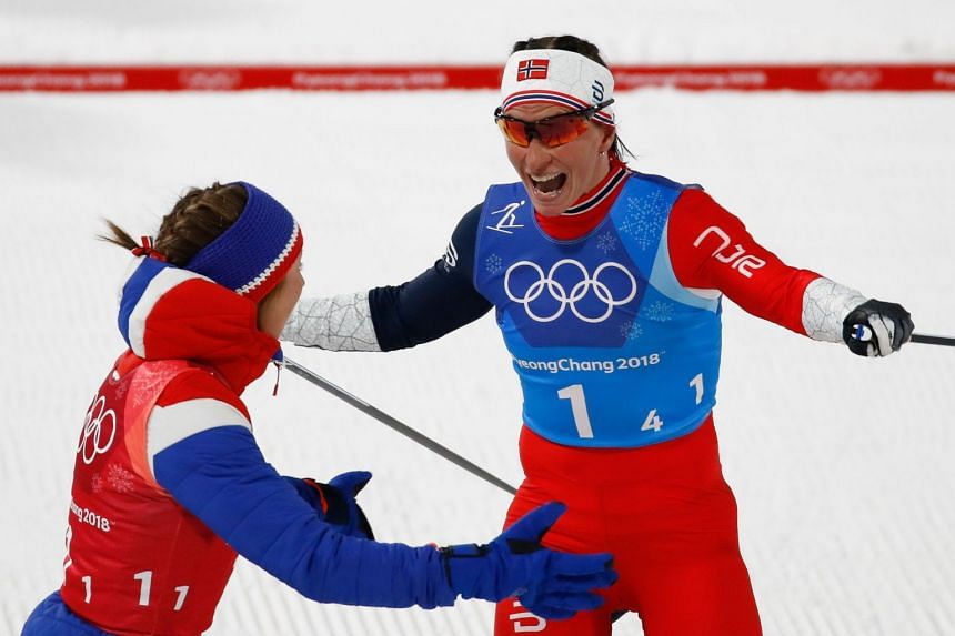 Norway's Marit Bjorgen (right) celebrates after winning the women's 4x5km classic free style cross country relay at the Alpensia cross country ski centre during the Pyeongchang 2018 Winter Olympic Games on Feb 17, 2018.