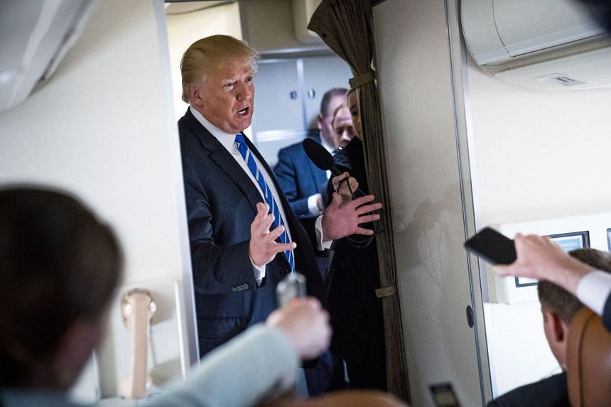 Trump speaks to reporters aboard Air Force One en route back from an event in West Virginia.