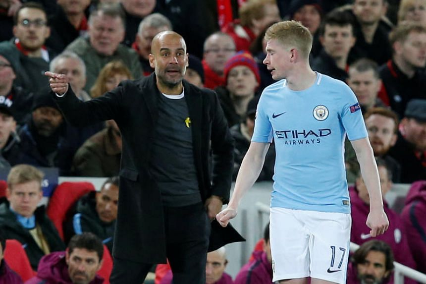 Manchester City manager Pep Guardiola gives instructions to Kevin De Bruyne.