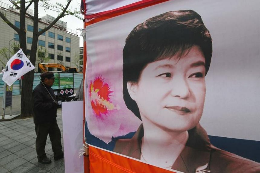 A supporter of South Korea's former President Park Geun Hye holding a national flag next to her portrait outside the Seoul Central District Court in Seoul on April 6, 2018.