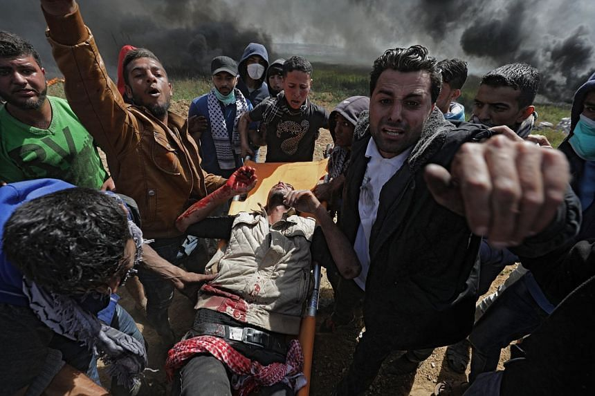 Palestinians protesters carry a wounded fellow demonstrator during clashes with Israeli troops.