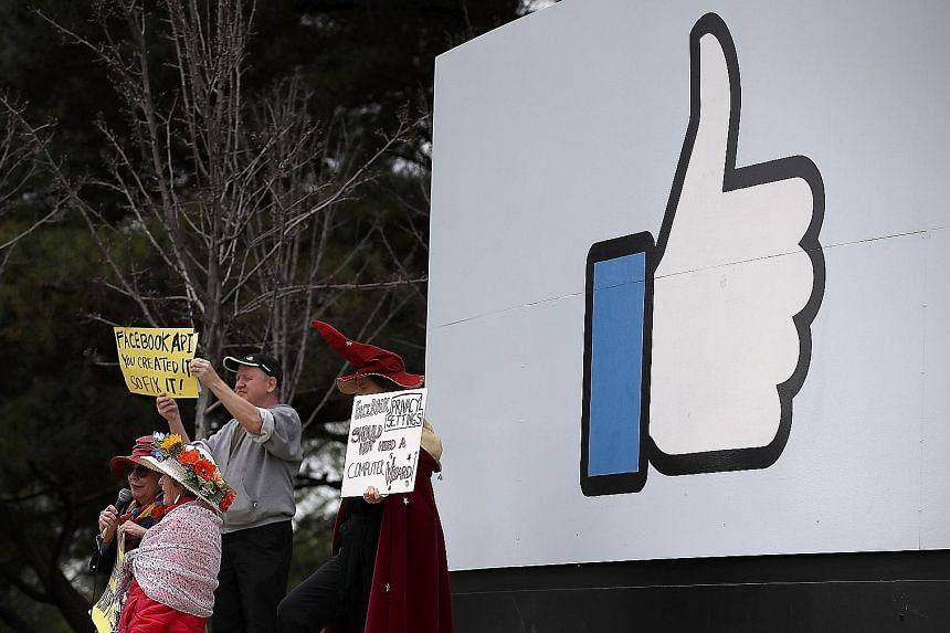 Protesters (above and below right) outside Facebook headquarters in Menlo Park, California, on Thursday calling for better consumer protection and online privacy in the wake of Cambridge Analytica's unauthorised access to the data of up to 87 million