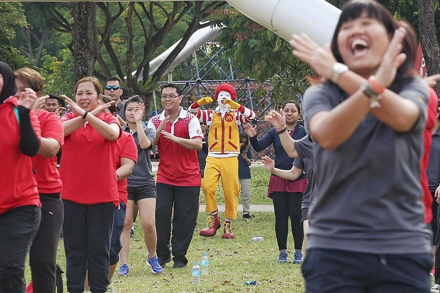 More than 100 McDonald's employees taking part in a mass workout session at West Coast Park yesterday morning. McDonald's is GetActive Singapore's first partner for this year, and plans to hold family-targeted fitness sessions at several of its outle