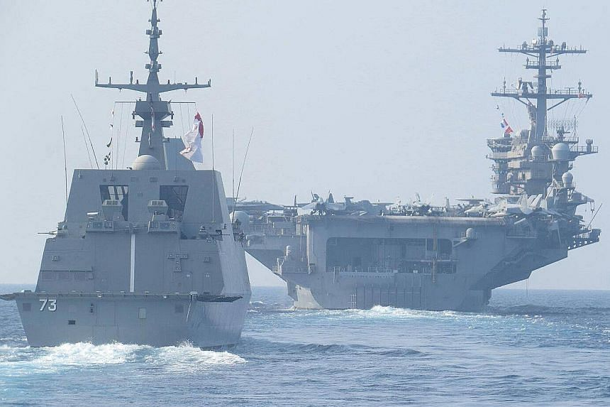The RSS Supreme Formidable-class frigate (left) sailing in formation with the USS Theodore Roosevelt aircraft carrier. They are taking part in a passage exercise between the Singapore and US navies.
