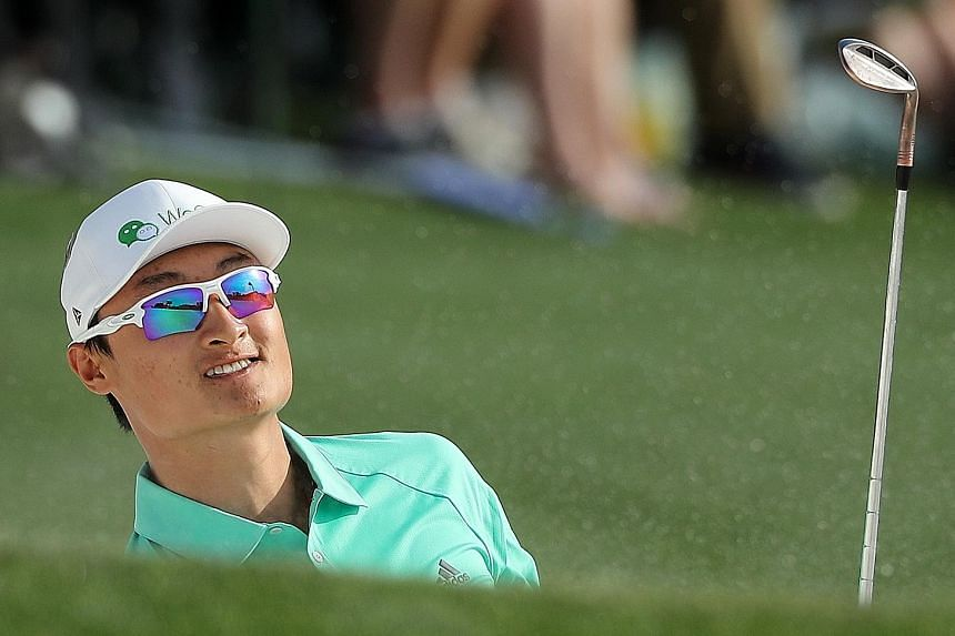 China's Li Haotong watches his chip shot land on the 18th green during the first round of the Masters tournament at the Augusta National Golf Club on Thursday. The 22-year-old's three-under 69 catapulted him to tied fourth.