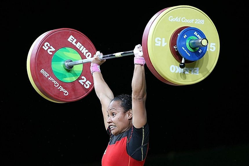 Dika Toua of Papua New Guinea competing in the 53kg final at the Commonwealth Games yesterday. She took silver by lifting 80kg in snatch and 102kg in clean and jerk.