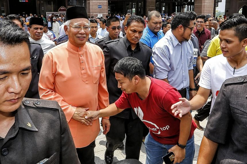 Prime Minister Najib Razak with supporters after Friday prayers in Putrajaya yesterday. Analysts say support from the lower income is likely due to the Najib administration pouring billions into welfare programmes such as direct cash aid, subsidies f