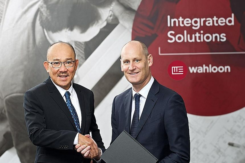 Wah Loon's founder and managing director Alan Chong, seen here with Vinci Energies Asia Pacific's managing director Eric Devigne, will continue to run the firm after the sale to Vinci Energies, a unit of French construction giant Vinci.
