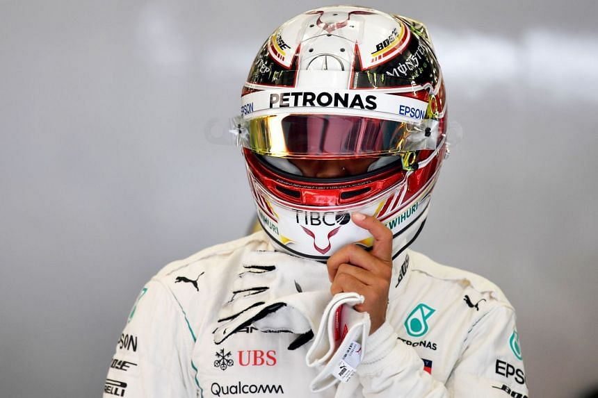 Hamilton prepares to enter his car during the first practice session in Bahrain.