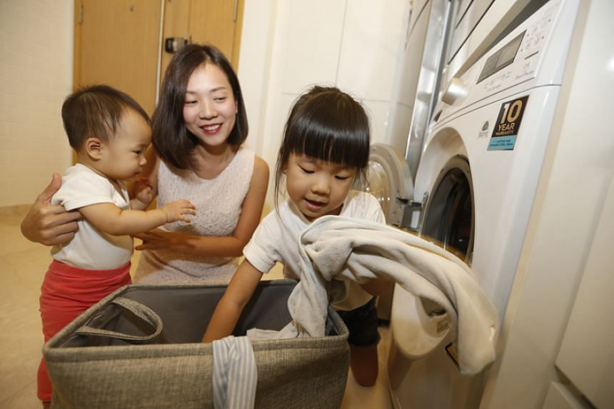 Ms Ashlyn Thia, with daughters Avalyn (left) and Emmalyn (right), separates adult laundry from the children's before each wash.