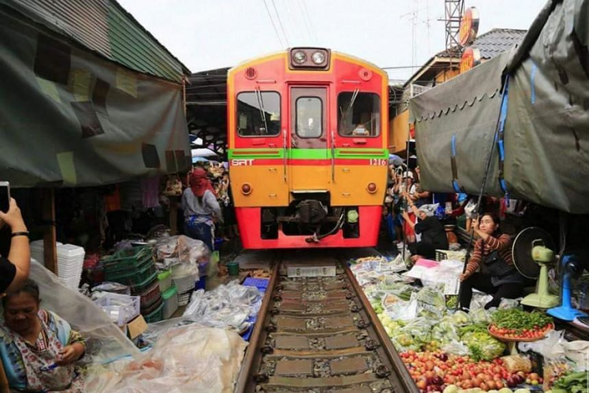 As part of the unique character and location of the market, some trays of produce remain partly under a moving train when it slowly moves past.