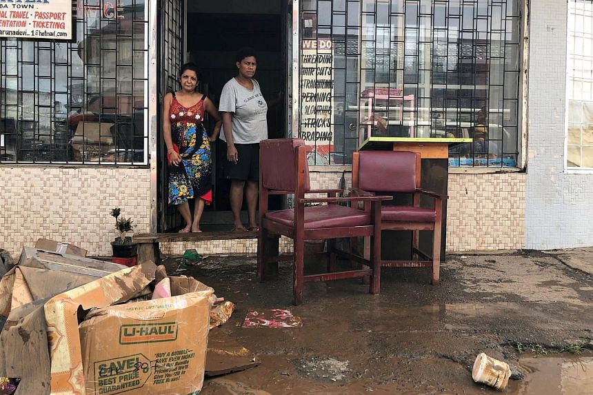People standing outside a business after flooding from Tropical Cyclone Josie in Ba, Fiji, on April 2, 2018.