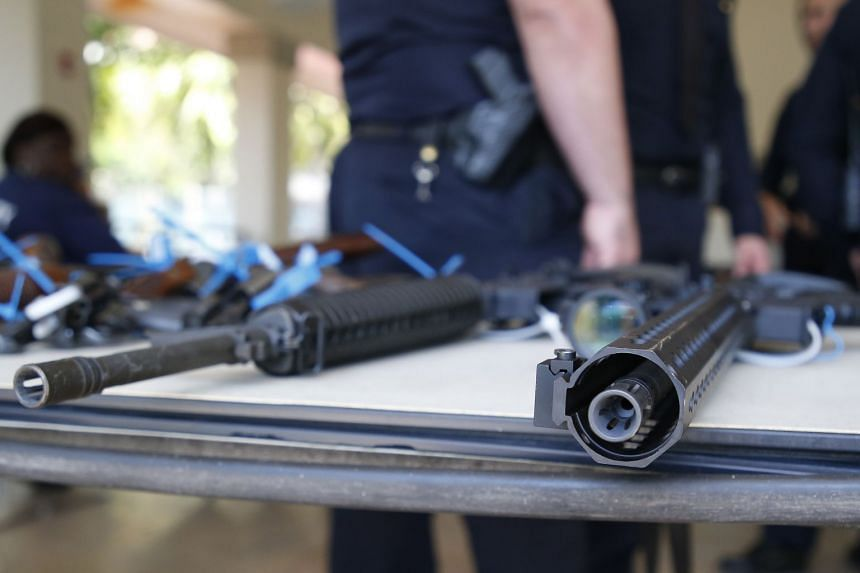 AR-15 rifles sit on a table after being surrendered during a gun buy-back event in Miami, Florida, on March 17, 2018.