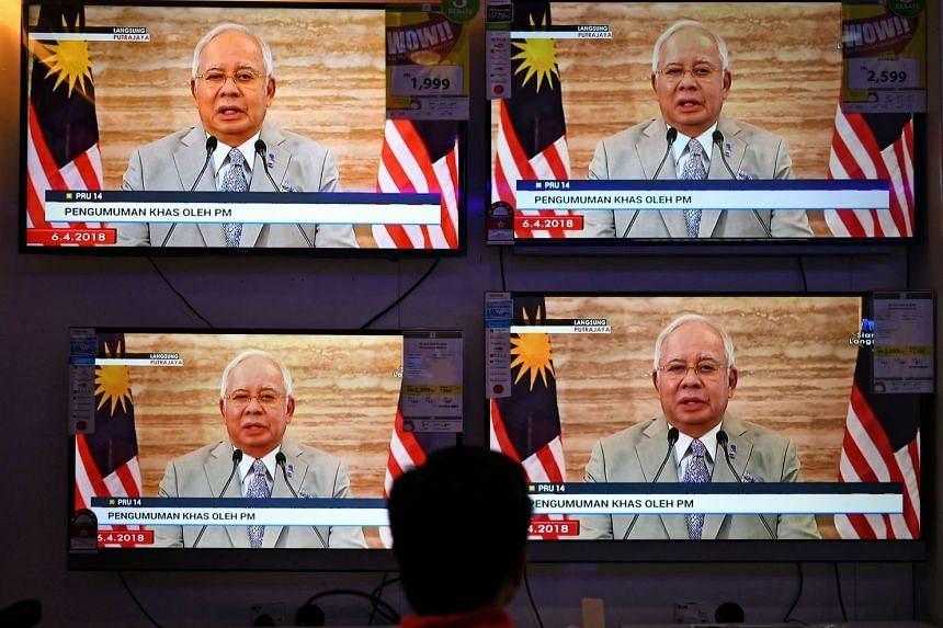 A man watches televisions on display at a shopping mall store as Malaysian PM Najib Razak announces the dissolution of Parliament in Kuala Lumpur, on April 6, 2018.