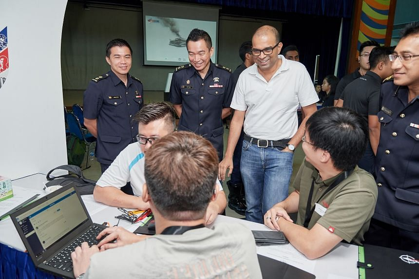 Senior Minister of State for Communications and Information Janil Puthucheary (standing, third from left) with attendees of a community emergency preparedness exercise on April 7, 2018.