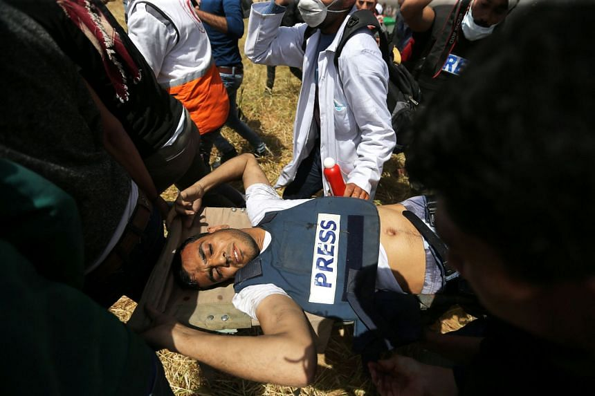 Mortally wounded Palestinian journalist Yasser Murtaja, 31, is evacuated during clashes with Israeli troops.
