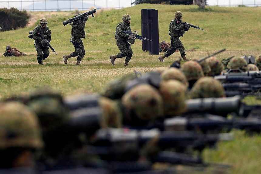 Japanese troops from the Ground Self-Defence Force's Amphibious Rapid Deployment Brigade in a drill on the south-western island of Kyushu yesterday.