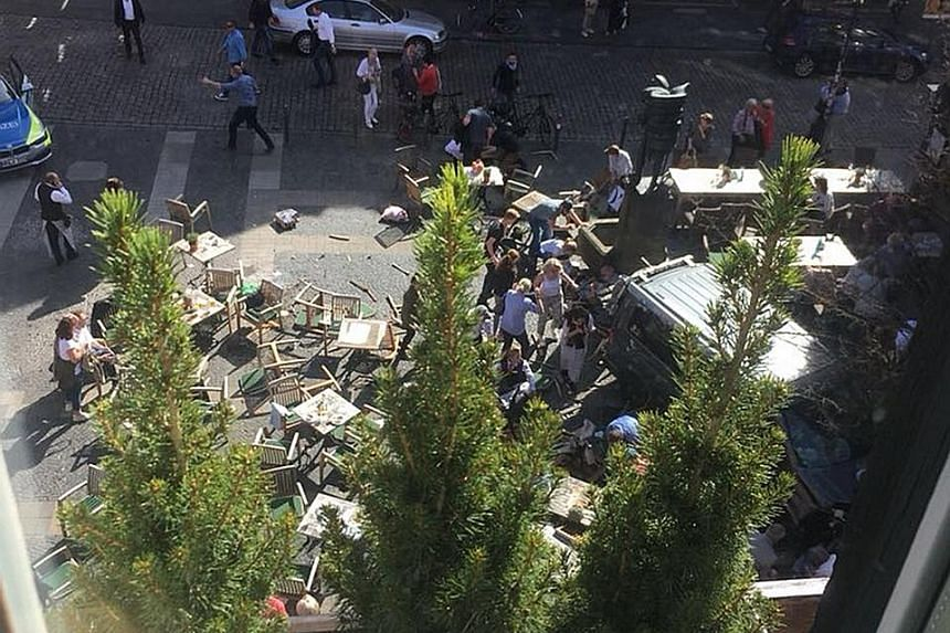 People gathering around several of the injured at the scene of the incident. The van drove into people sitting at tables outside the Grosser Kiepenkerl restaurant, which is popular with tourists, said police.