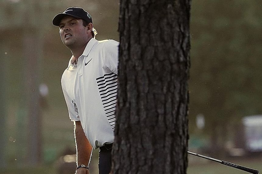 American Patrick Reed looking out from behind a tree on the 17th fairway during the second round of the Masters golf tournament on Friday.