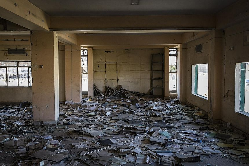 (Left) One of the land leases which the Islamic State in Iraq and Syria had stolen from members of religious groups it chased out. (Far left) Paperwork littering Mosul's bombed-out Ministry of Agriculture last September.