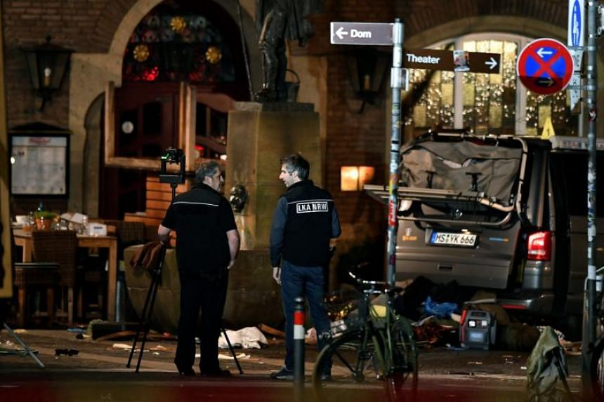 Members of the state office of criminal investigation in North Rhine-Westphalia are seen at the crime scene in the inner city of Muenster, Germany on April 8, 2018.
